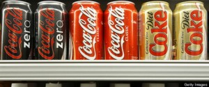 Cans and bottles of Coca-Cola are displayed in a grocery sto